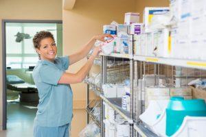 The nurse looks for a specific medicine.